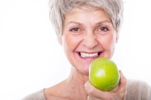Woman holding apple after transitioning to dental implants